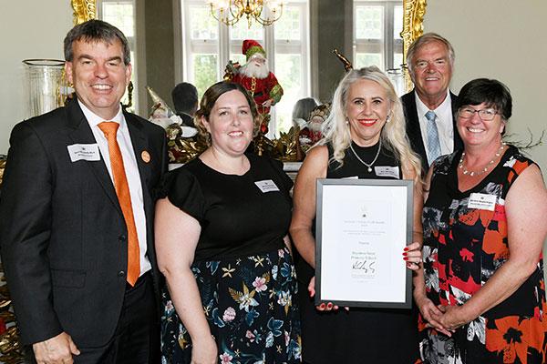 A small group of women receiving an award.