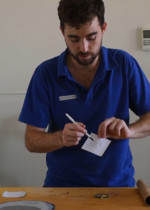 A man in a blue shirt drawing a constellation on a small square piece of paper.