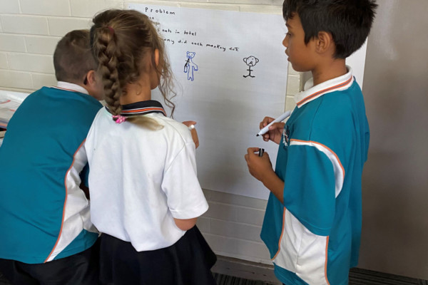 Three primary school children writing on a white board and discussing mathematics.
