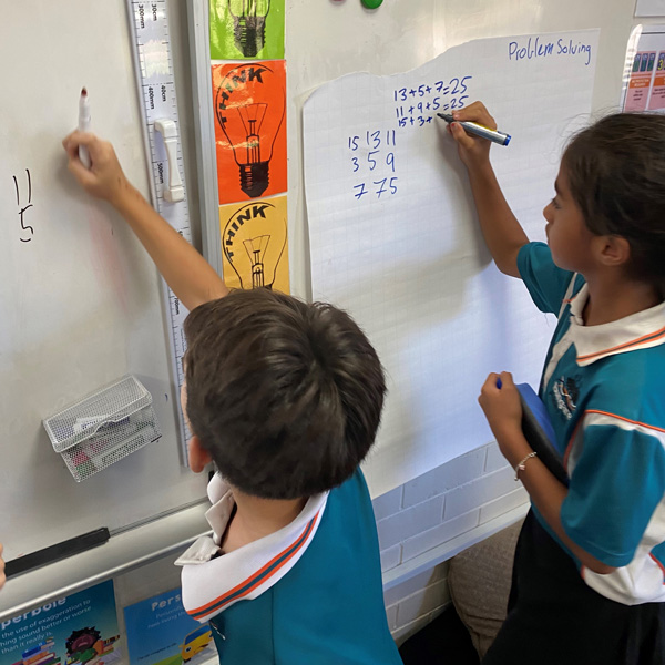 Two primary school children in a classroom writing numbers on a white board.