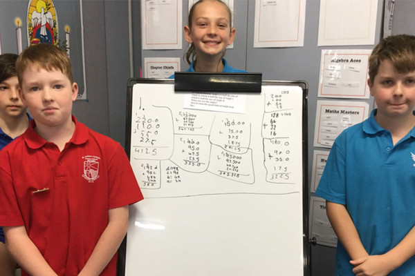 Three primary students standing next to a white board showing math problems they have written.
