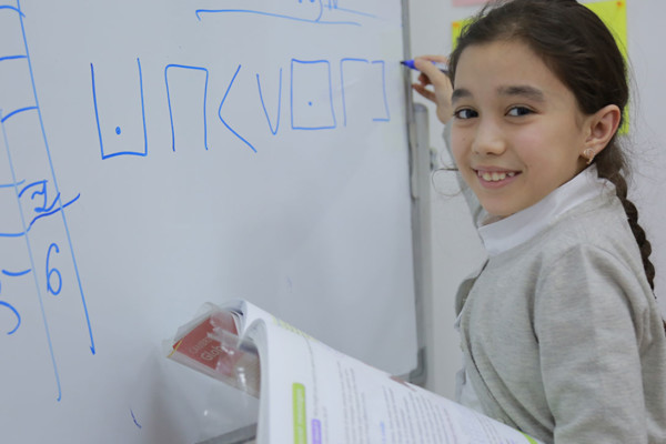 A young girl drawing shapes on a whiteboard whilst holding a textbook and smiling at the camera.