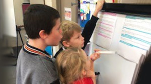 Three students in a classroom problem solving on a whiteboard together.