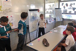 A young student explaining a project to other students in a classroom.