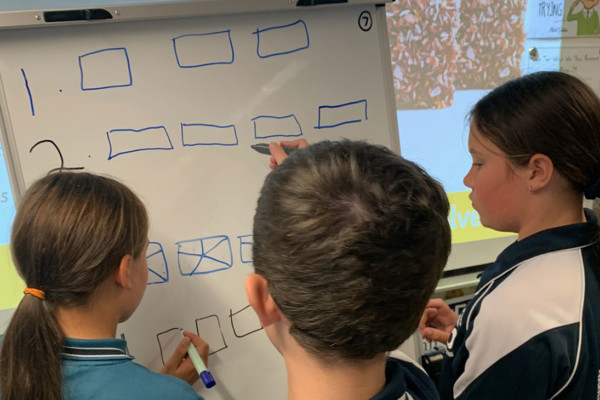 Three primary aged students in a classroom solving math problems on a white board.