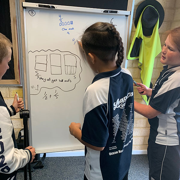 Three primary school children drawing fractions on a whiteboard.