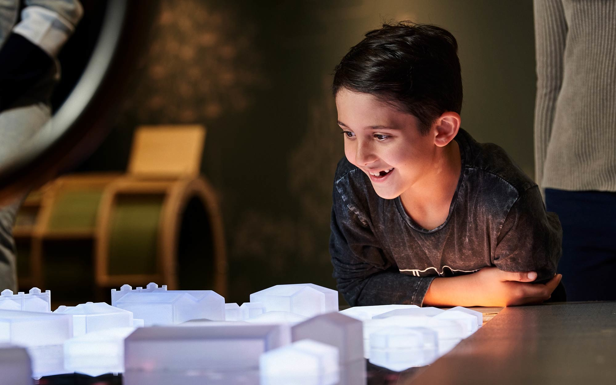 Boy amazed at 3D printed buildings lit up by LED lighting