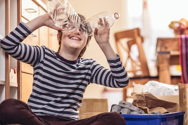 Caucasian boy sitting on the kitchen floor, sorting out the recycling in to blue box. He is holding two plastic bottles on his face, pretending to look thru binoculars. Sunny day interior.