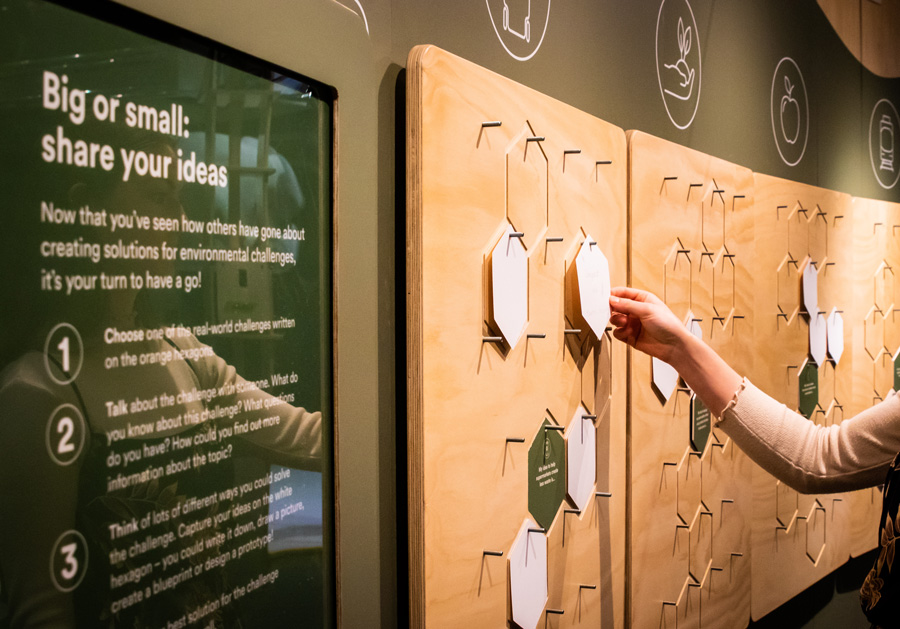 Hand placing written ideas about sustainability on a wall