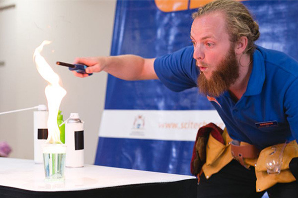 Scitech science presenter blowing on a flame on stage.
