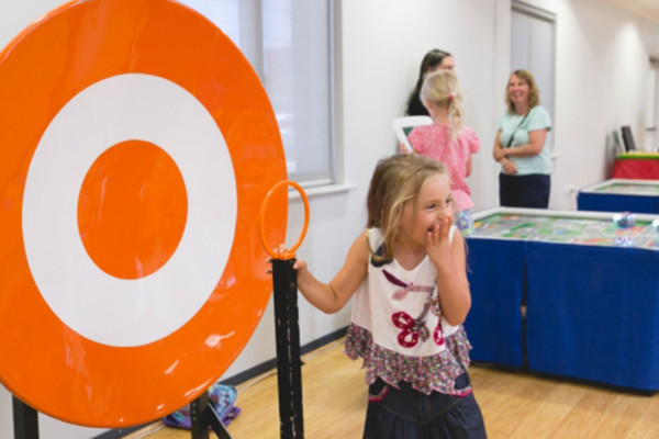 A young girl playing next to a large target sign.