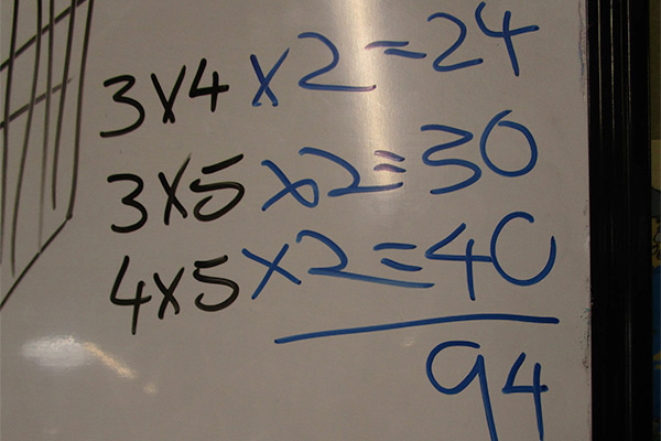 Closeup of multiplication equations on a whiteboard.