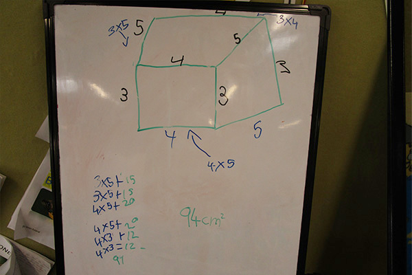 A 3d rectangular shape with dimensions annotated on a whiteboard.