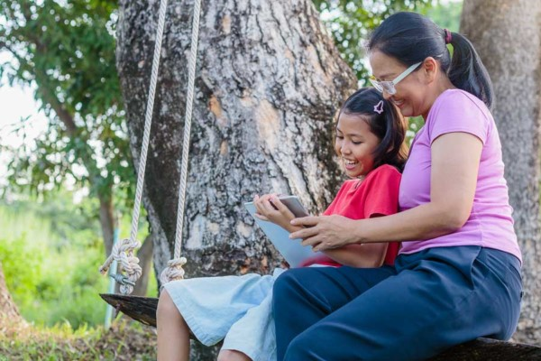 A woman and child reading a book next to a tree on an outdoor swing.