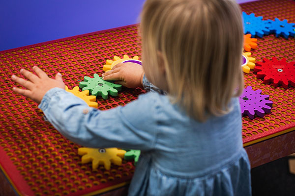 A toddler playing with coloured cogs on a table in Discoverland.