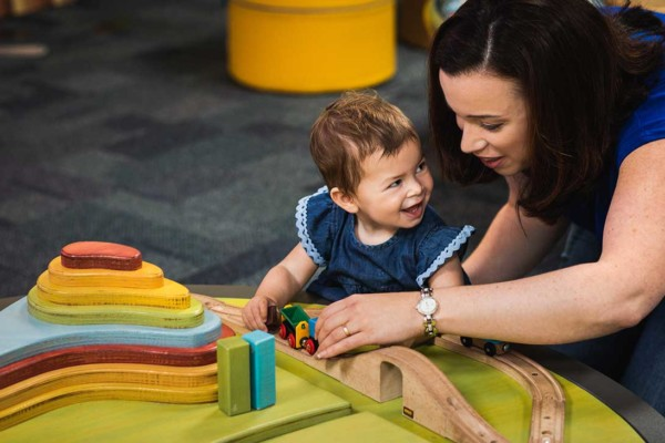 A mother in Discoverland showing her toddler how to play with coloured wooden blocks, the toddler is excited.