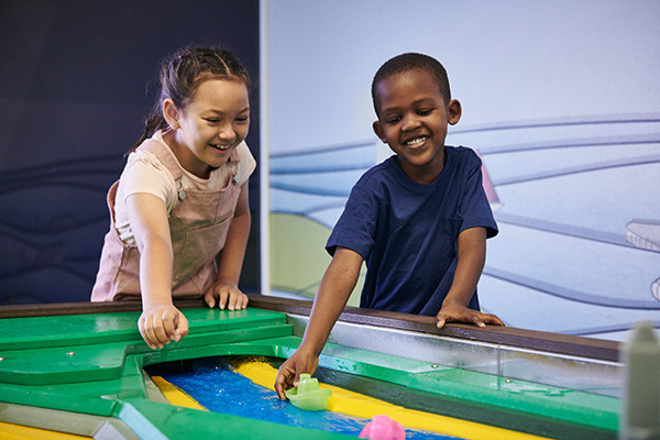 Two young children playing in Discoverland in a water exhibit with rubber ducks.