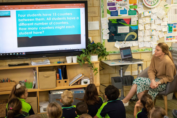 A teacher showing a primary classroom a powerpoint presentation.