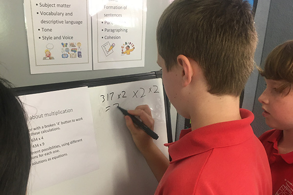 A young male primary student writing maths equations on a whiteboard.