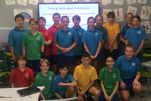 A classroom of year 6 primary students smiling for a group photo.