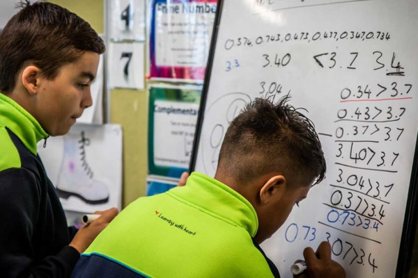 Two primary student boys writing math symbols on a small whiteboard.