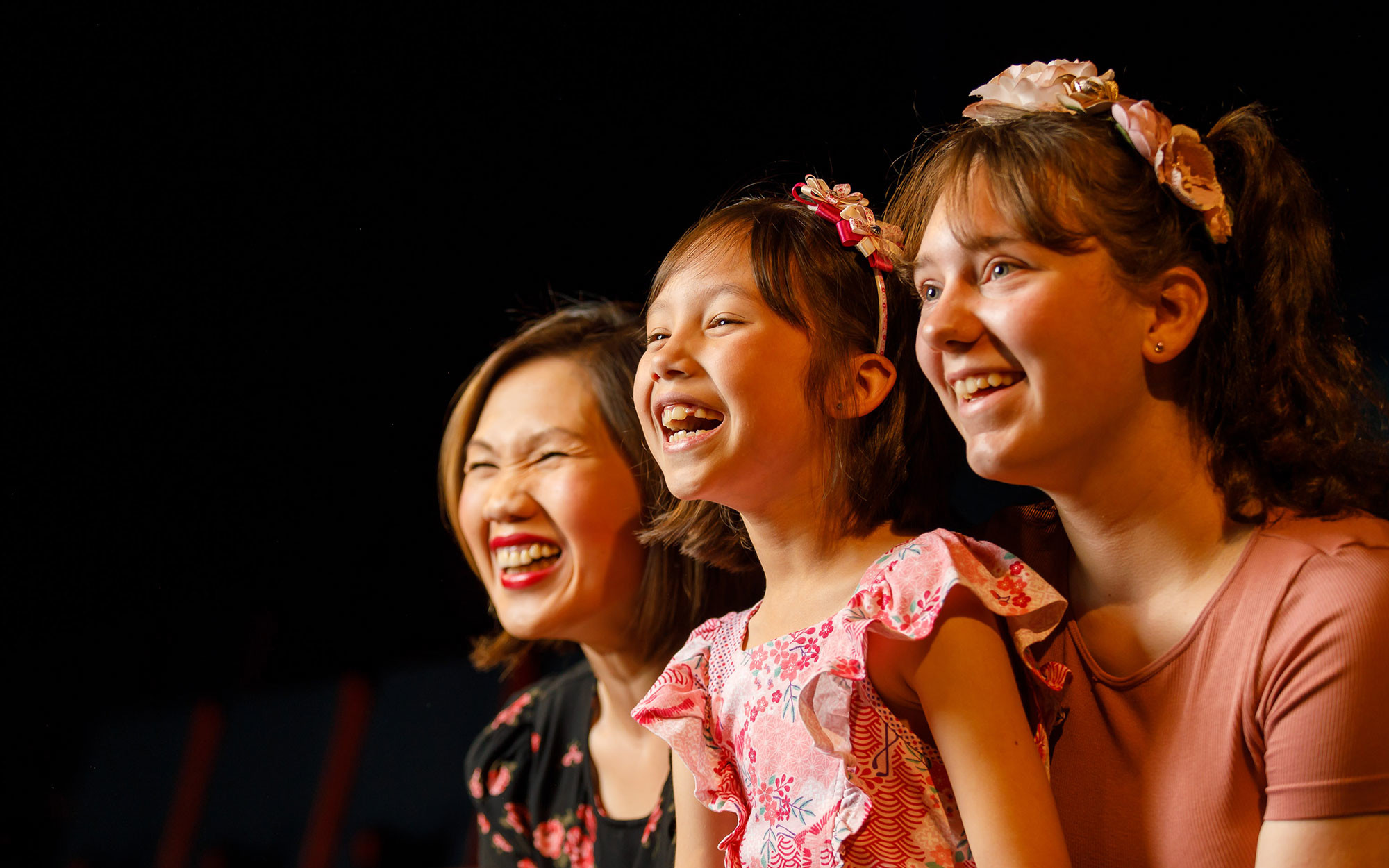 A mother and her two children laughing and smiling enthusiastically together.