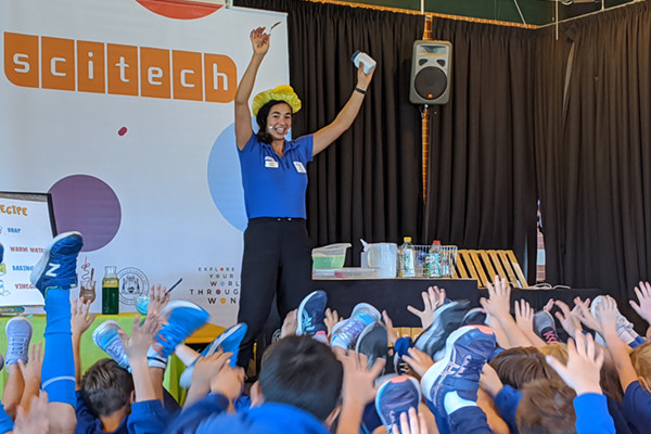 Science presenter excitingly presenting a show in front of primary students