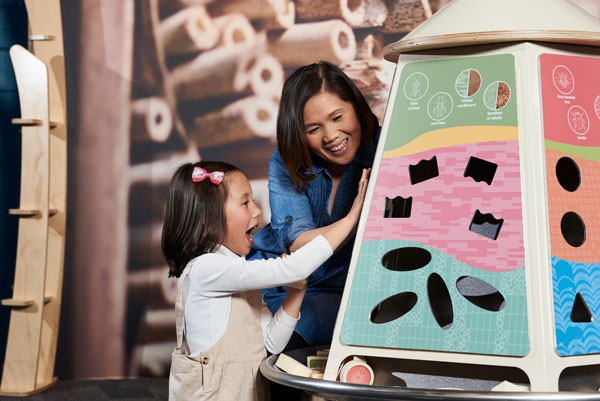 Toddler and mum exploring a colourful shape sorter activity