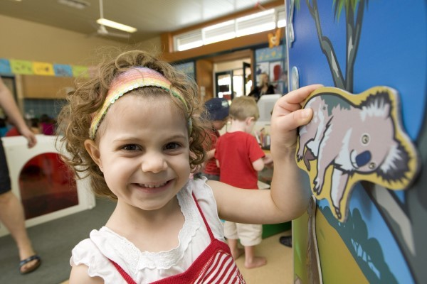 Smiling toddler participating in an early childhood workshop