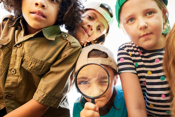 A group of four children look at the camera, one has a magnifying glass