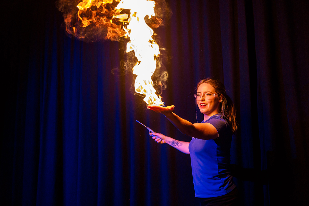 Scitech science presenter holing fire in their hand as part of a science show