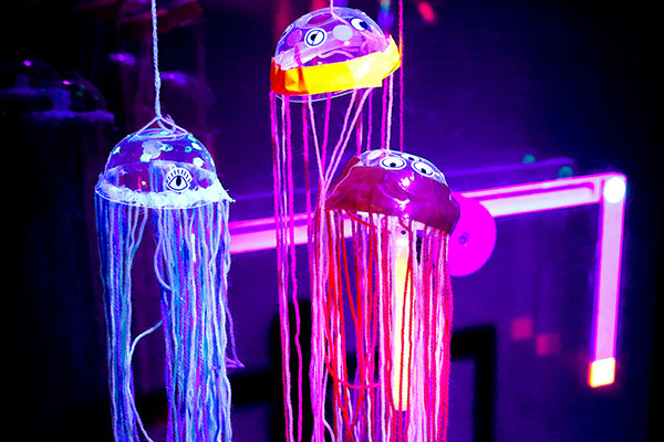 Three handmade glow-in-the-dark jellyfish made from plastic cup tops and string