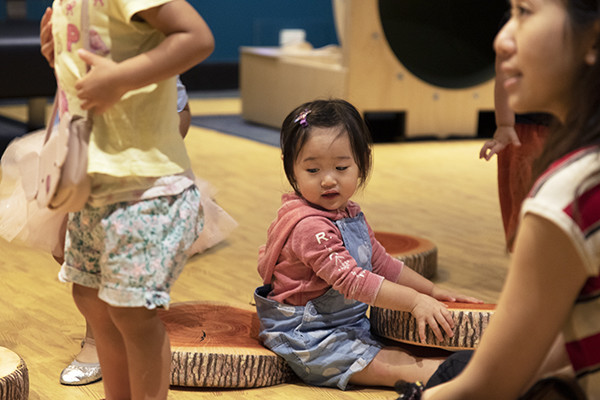 A toddler wearing a pink hoodie sits on a cushion that looks like a piece of log wood